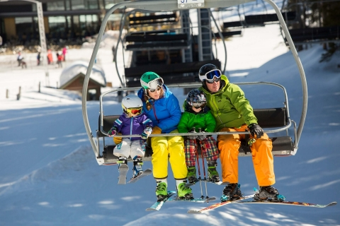 Family rides a chairlift at Aspen Snowmass.