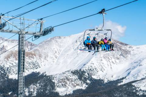 Skiers and snowboarders ride a lift at Winter Park Resort.